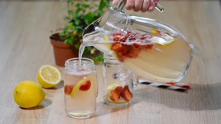 infused water : Strawberry lemonade with ice in mason jar on a wooden table.