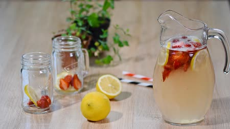 cítrico : lemonade with strawberries, lemon and ice in a glass jug.