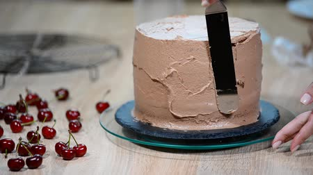 palette knife : Step-by-step preparation of black designer cake. The confectioner covers the cake with cream. Stock Footage
