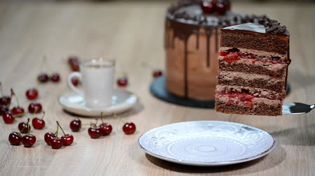wisnia : Putting a piece of cherry chocolate cake in a plate.
