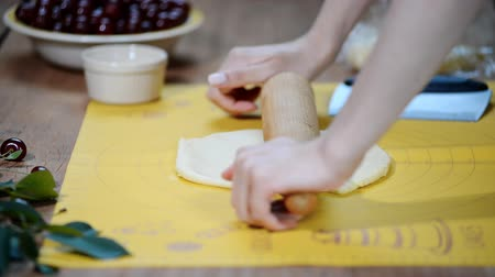requintado : Woman hands roll out the dough on the kitchen table to make a pie with berries.