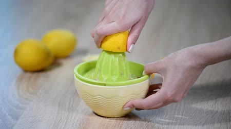 squeezer : Womens hand in the kitchen clutching a lemon.