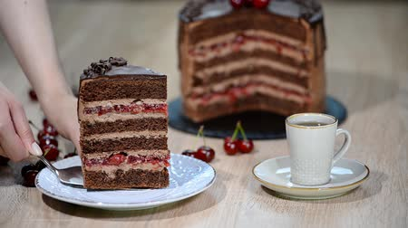 полосатый : Putting a piece of cherry chocolate cake in a plate.