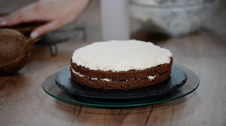 palette knife : Womans hand spreading whipped white cream on chocolate sponge cake. Stock Footage