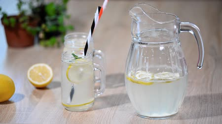 infused water : Lemonade or mojito cocktail with lemon and mint, cold refreshing drink or beverage with ice.