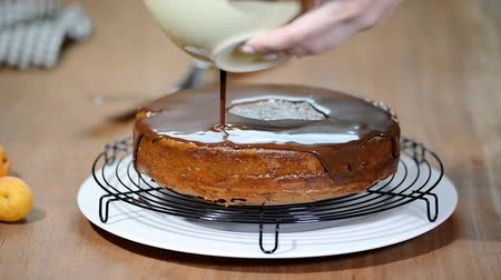 servido : Making Sacher cake - traditional Austrian chocolate dessert. Pouring chocolate glaze