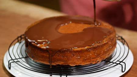caloric : Making Sacher cake - traditional Austrian chocolate dessert. Pouring chocolate glaze.
