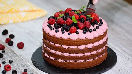 námraza : Cutting beautiful chocolate cake with fresh berry.
