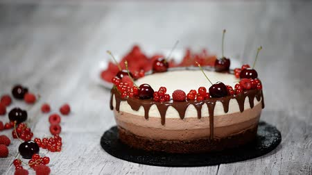 hármas : Triple chocolate mousse cake decorated with fresh berries.