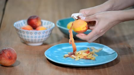 kompot : Female hands peeling a blanched peach.