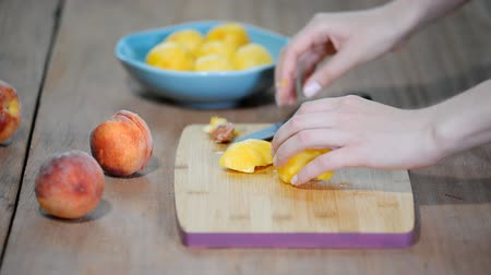 konzervipar : Slicing organic peach on wood cutting board. Stock mozgókép