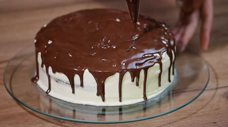 receita : Woman pours melted chocolate on a chocolate cake.