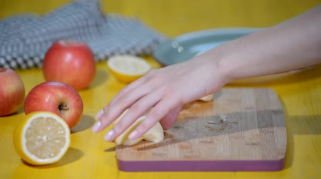 segmento : Cutting Apple into pieces on a cutting board.