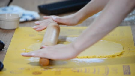 песочное печенье : Womens hands roll the dough on the kitchen table.