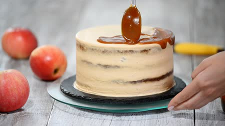 çırpılmış : Young woman applying caramel sauce onto delicious homemade cake at table. Delicious cake with apple and whipped cream filling.