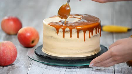 šlehačka : Young woman applying caramel sauce onto delicious homemade cake at table. Delicious cake with apple and whipped cream filling