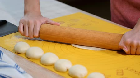taco : Woman roll out the dough on the table. Step by step recipe of homemade tortillas.