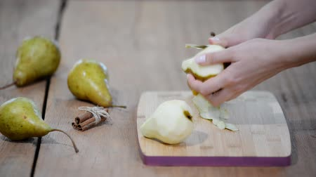 apologize : Peeling pears with a white vegetable peeler.