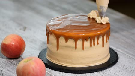 šlehačka : Close-up of woman decorating cake. Making Caramel Apple Cake. Dostupné videozáznamy