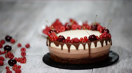 домовой : Three chocolate mousse cake decorated with berries.