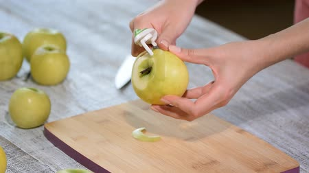 soyulmuş : Hands peeling a cooking apple on a wooden board.