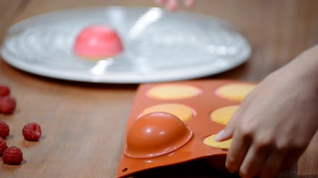 sweetened : Hands taking mousse cakes out of a flexible silicone mold. Making French dessert. Stock Footage