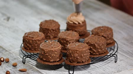 домовой : Decorating chocolate mini mousse cake. Chocolate Hazelnut Mousse Cake covered with chocolate glaze.