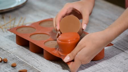 consistency : Hands taking mousse cakes out of a flexible silicone mold.