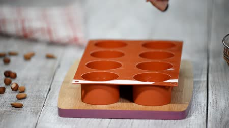 sweetened : Female hands filling a silicone mold with a chocolate mousse. Making French dessert.