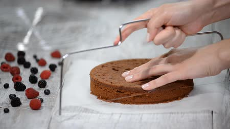 stapelen : Chef cutting chocolate cake layers and stacking them.