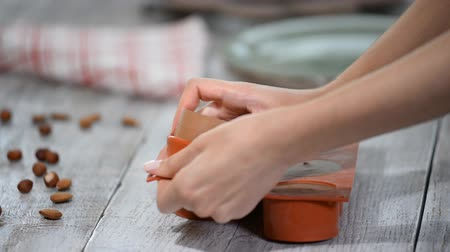 смесь : Hands taking mousse cakes out of a flexible silicone mold.