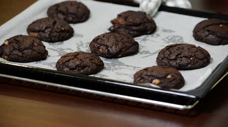 parşömen : Freshly baked chocolate cookies on the baking sheet on a table close-up.