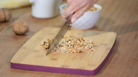 čištěný : Female chefs hands chopping walnuts on wooden cutting board.