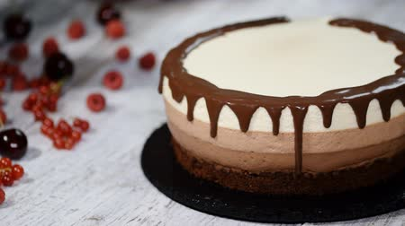 koláč : Triple chocolate mousse cake decorate with a melted chocolate.