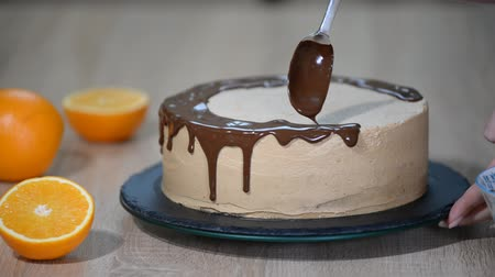 jegesedés : Chef squeezes cream. Chocolate icing on the cake. White cake covered with chocolate and cream. Chocolate cake decoration. Stock mozgókép