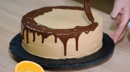 šlehačka : Chef squeezes cream. Chocolate icing on the cake. White cake covered with chocolate and cream. Chocolate cake decoration. Dostupné videozáznamy