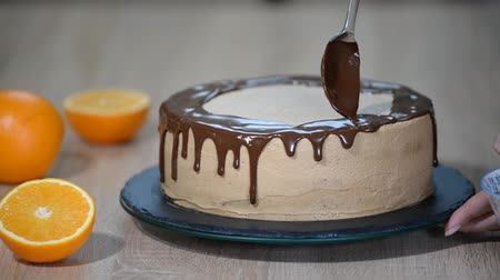 konfekció : Chef squeezes cream. Chocolate icing on the cake. White cake covered with chocolate and cream. Chocolate cake decoration. Stock mozgókép