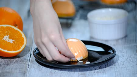 malina : Process of creating delicious dessert. Unrecognizable confectioner hands decorate orange glazed cakes.