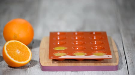 befőz : Pouring orange jelly in the silicone mold.