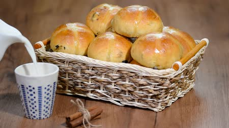 krentenbol : Pasen Hot Cross Buns in een mandje. Giet melk in een kopje. Stockvideo