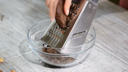 ralado : Woman grates chocolate dough in the glass bowl. Stock Footage