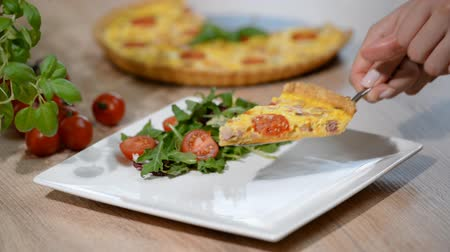 potraviny : A piece of French quiche Lorraine. Quiche Lorraine with salad