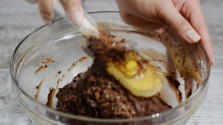 fornada : Girl stirs chocolate dough with spatula. The process of making chocolate batter.