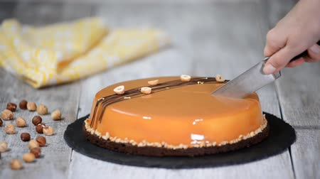 фундук : Female hand cutting the caramel mousse cake. Caramel cake, mousse dessert on a plate. Mousse cake with a mirror glaze