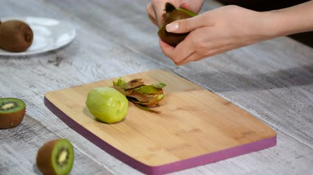panelas : A woman cleans the kiwi peel with a knife on a wooden background.