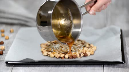 засахаренный : Pouring caramel on hazelnuts. Step by step. Making praline on the kitchen. Стоковые видеозаписи