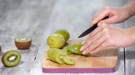 kool : Hand slicing a kiwi with a knife, close up.