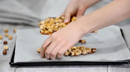 cukrozott : Female hands breaking hazelnuts into caramel into pieces. Stock mozgókép