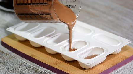 sweetened : Female hands filling a silicone mold with a chocolate mousse, close-up. Making French dessert. Stock Footage