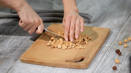 calorias : Female chefs hands chopping hazelnuts on wooden cutting board. Stock Footage